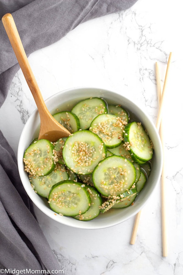 Asian Cucumber Salad in a bowl with a wooden spoon