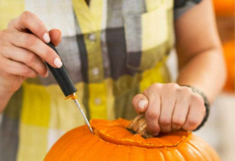 Closeup on person in a Halloween decorated kitchen carving a big orange pumpkin Jack-O-Lantern