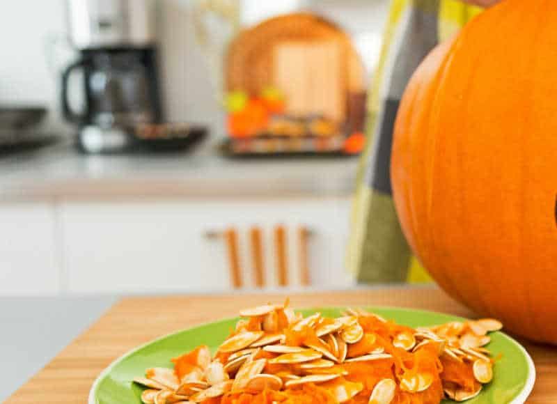 Closeup on young person in the Halloween decorated kitchen prepare big orange pumpkin for carving