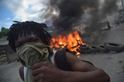 10/02 - Um manifestante diante de uma barricada de pneus em chamas no quarto dia de protestos em Porto Príncipe / Foto: EPA