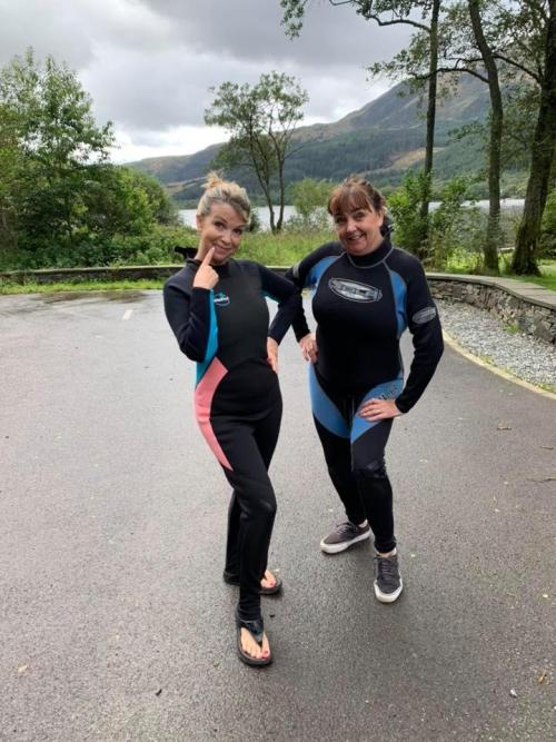Two female Wild Swimmers in wetsuits, with lake and mountains behind them