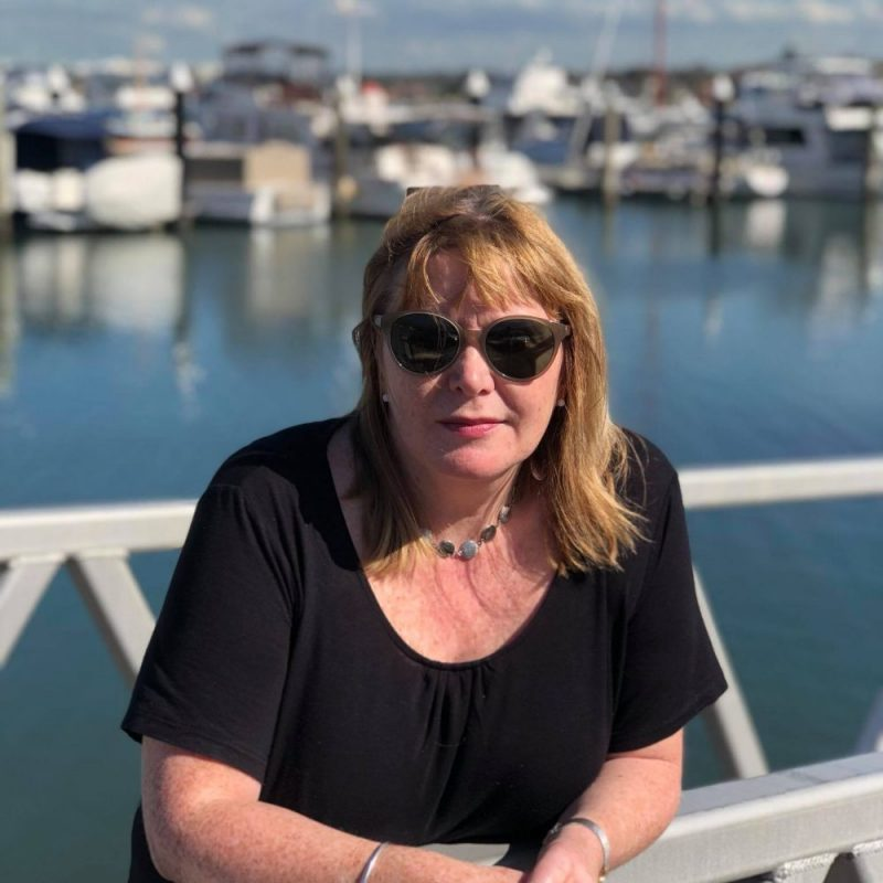 Woman in sunglasses in Harbour setting after Emigrating to Australia