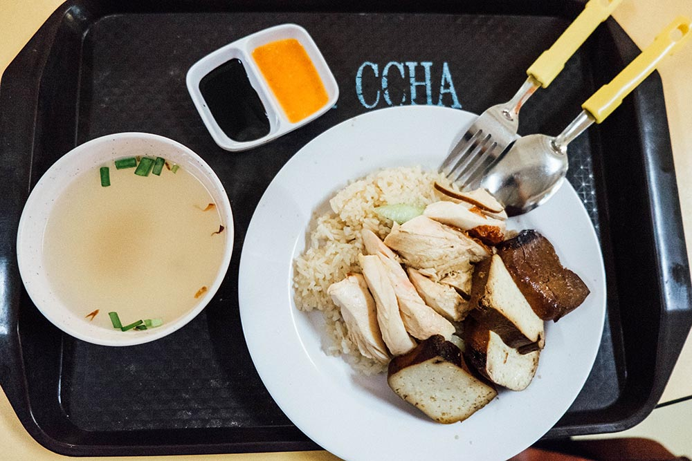 Chicken rice dish on a black tray with dipping sauce
