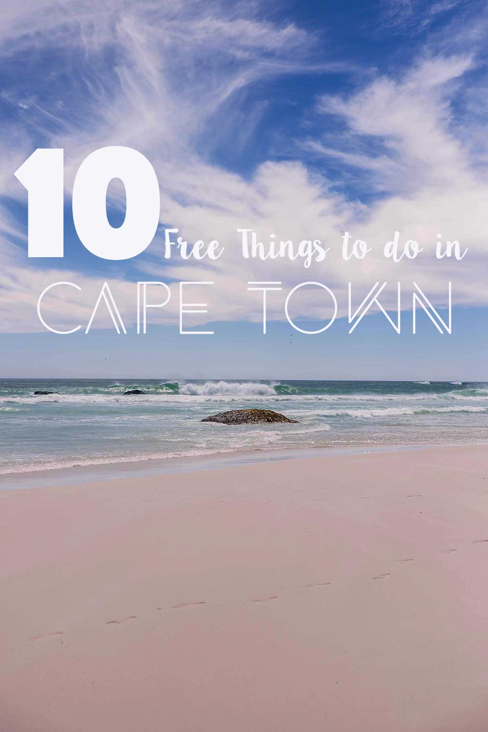 Boulder in the ocean on the beach with waves crashing with text overlay - 10 free things to do in Cape Town.