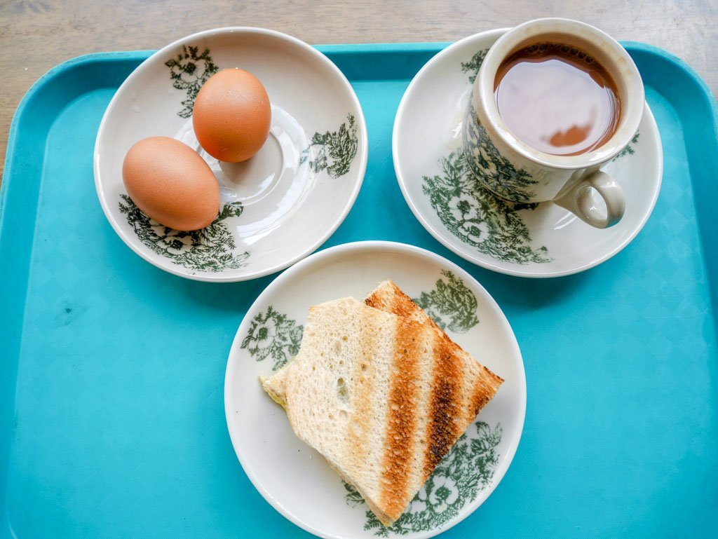 Blue tray with a cup of tea, a plate of toast and a plate with two eggs