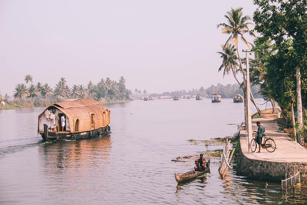 Kerala back waters with a canoe and man on the bike - Great Indian Blog Train
