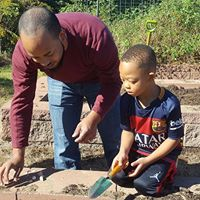 A father and son planting garlic at the Ghouls & Garlic event.