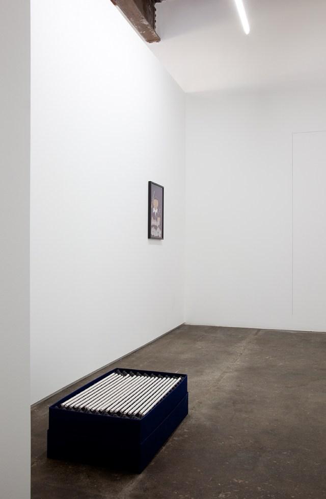 David Catherall, installation view. Foreground: [ IIIIIIIIIIIIIIIIIII ], 2012. 19 hand-rolled unglazed porcelain objects, buckram covered boxes, foam, latex paint. 30 x 18 x 9 ½ inches. Background: / Fixer, 2012. Gouache, watercolour paper, artist frame. 13 ¾ x 23 ½ inches framed.