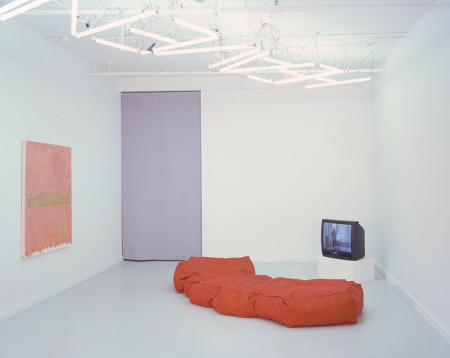 Michelle Hines and David Kramer, installation view. David Kramer, left to right: LLLucky, 2001. Oil on canvas; California Day Bed, 2000. Fabric, foam; Method Acting, 2002. VHS. 22 minutes. Edition of 6; Asshole, 2002. VHS. 6 minutes. Edition of 6. Ceiling: Heaven on Earth, 2001. Fluorescent bulbs and ballasts.