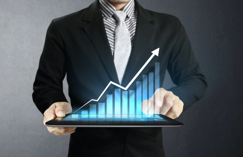 Man wearing a striped button down shirt with a white paisley tie and a black suit jacket holds a large tablet with a 3D bar graph displaying like a hologram above the screen white the man points at the tallest graph point
