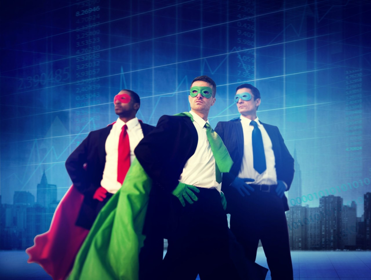 Three men in business professional attire, but also wearing a mask over their eyes and a cape blowing. Behind them is a blue tined cityscape with many graphs and numbers overlaying it