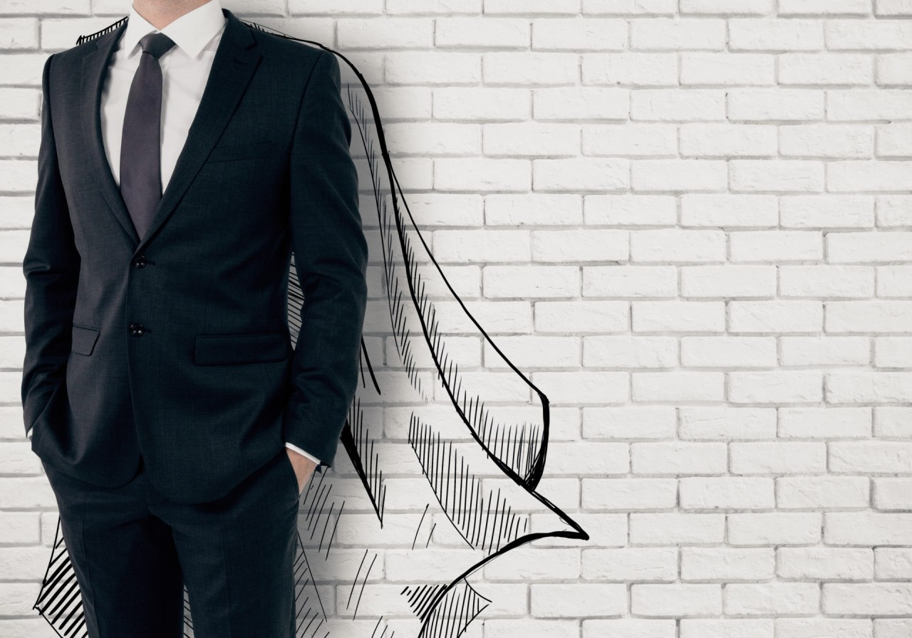 man in buisness suit with his hands in his pockets with a drawn cape on the white brick wall behind him