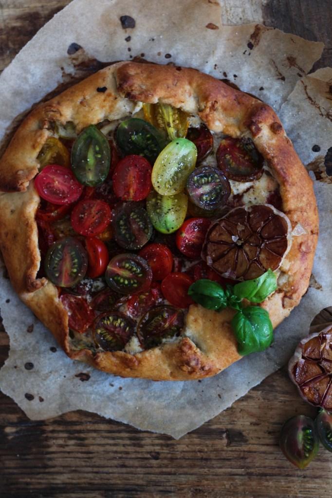 Galette {all'olio di oliva e pinoli} con pomodori, formaggio di capra e aglio arrosto