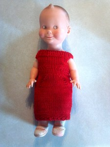 Baby doll in a red handknit dress.