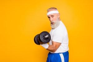 Señor con barba y cinta en la frente, levantando una pesa de gimnasio