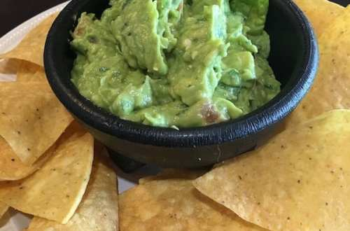A small bowl of guacamole surrounded by chips