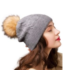 woman in a hat with a faux fur pom pom