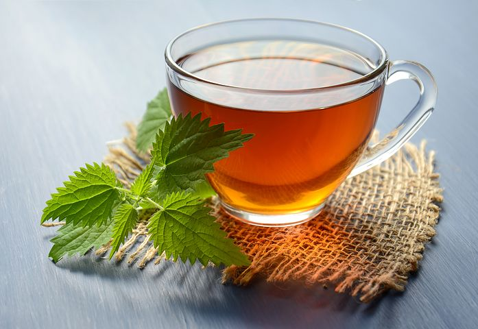 glass cup filled with the best tea for migraine with a green mint leaf on a cloth coaster