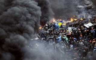 Ukrainian protesters stand behind burning barricades during a face-off against police in Kiev.