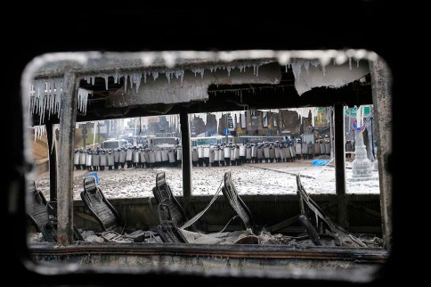 Seen through a vehicle torched by protesters overnight, police officers block a street during unrest in Kiev, Ukraine, on Jan. 20, 2014.
