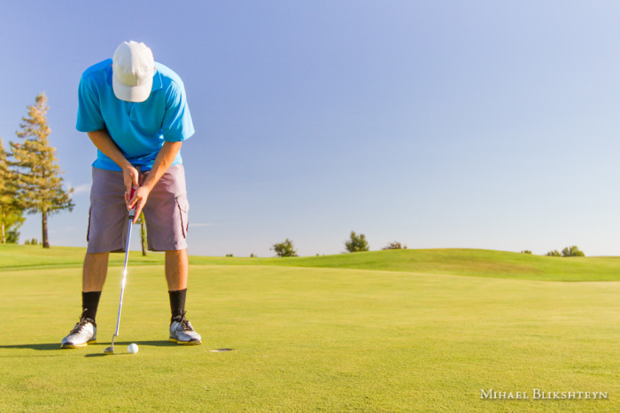 Man playing golf on a sunny day on a beautiful golf course