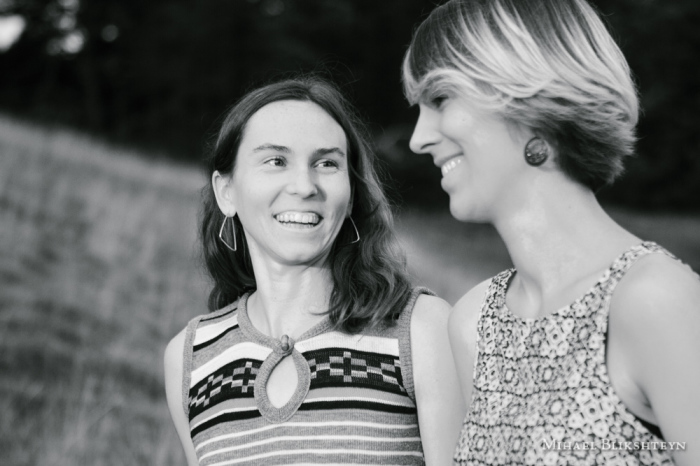 Black and white photo of two young women talking and laughing