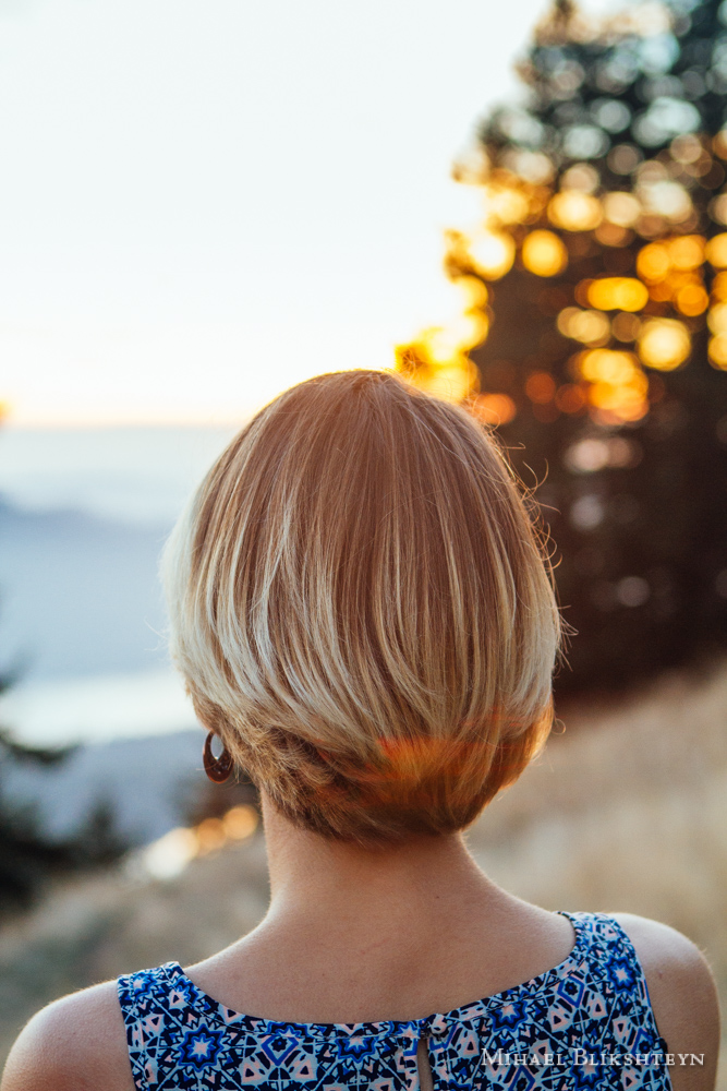 Back of a young woman's head and shoulders as she is watching sunset