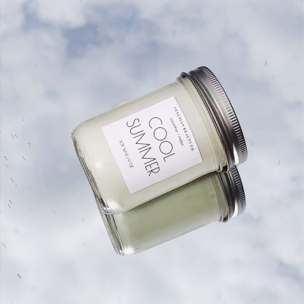 """candle in a mason jar with the words """"COOL SUMMER"""" written on a white label"""