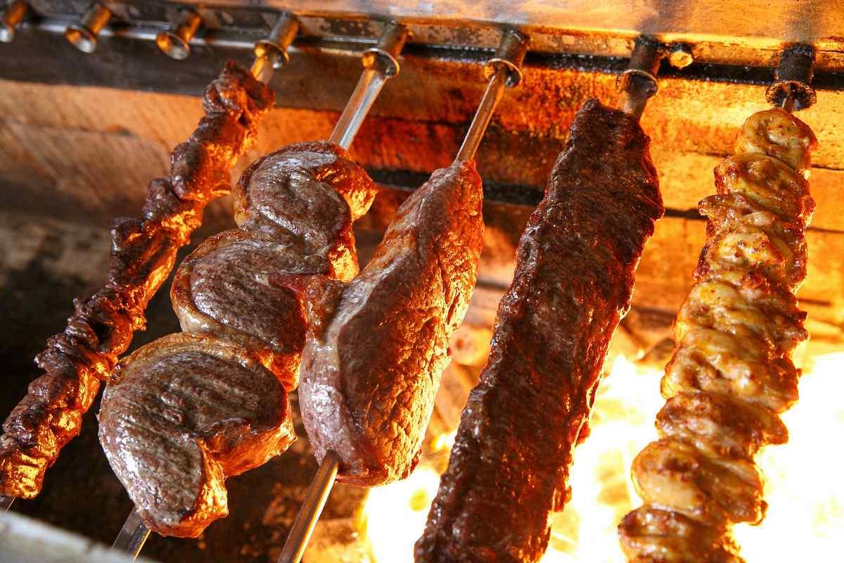 Braziliaanse vleesspiesen draaiend op het vuur bij de Rodizio