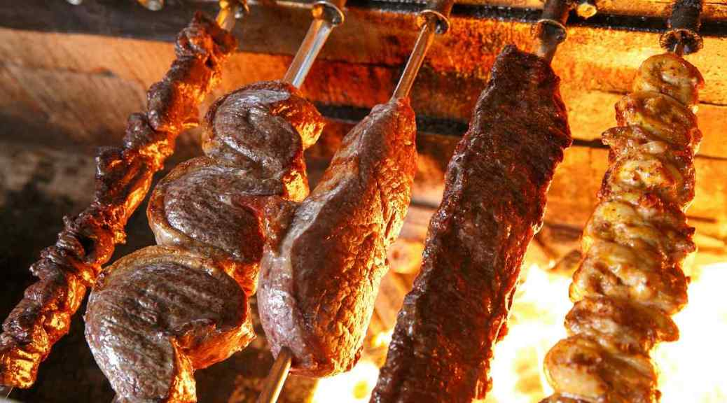 Vijf verschillende vleesspiesen draaiend op een grill