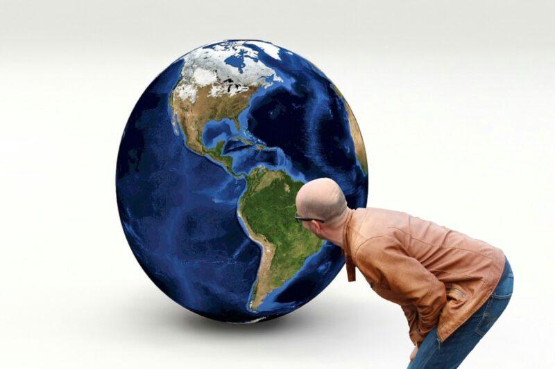 Man die naar de wereldbol kijkt waarop Zuid Amerika duidelijk te zien is