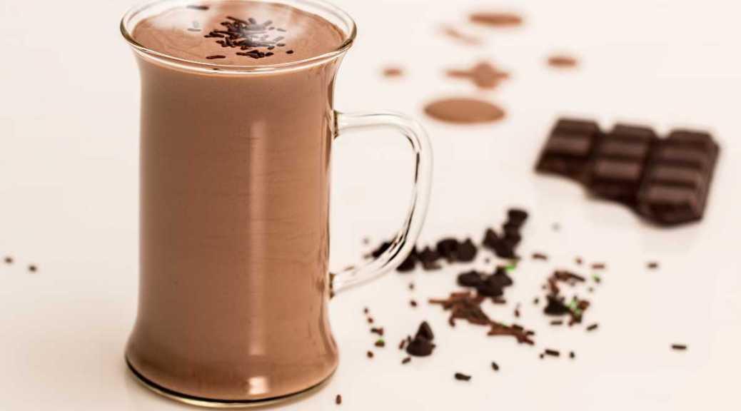 Braziliaanse warme chocolademelk in een glas met chocolade er om heen gepresenteerd