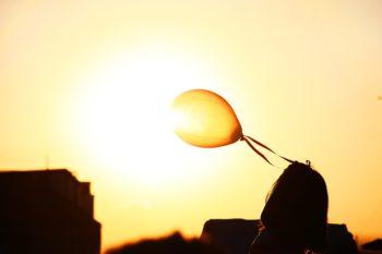 meisje met oranje ballon bij de zon