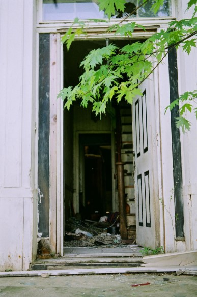 A closeup of the front door of an abandoned farm house.