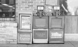 Just a basic shot of some newspaper machines could have been shot in 2017 or 1967.