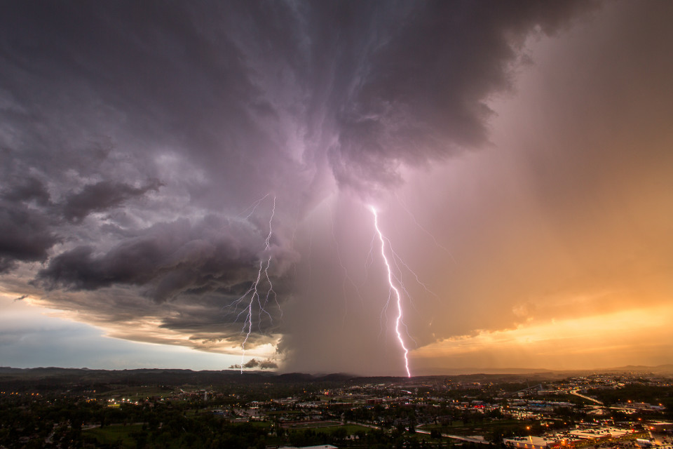 A decaying supercell hovers over the Rapid City, South Dakota area, dropping rain and gorgeous lightning bolts.