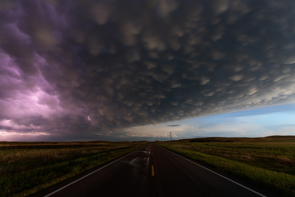 On a long, lonely highway between Merriman and Hyannis, Nebraska...a huge MCS moves by, leaving behind it wet roads and a gorgeous sky filled with mammatus clouds. A bit of lightning snakes around on the left side of the storm.
