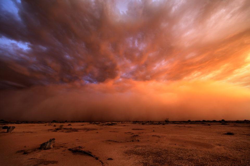 A late season haboob rolls towards Phoenix with the setting sun turning the dust and clouds all shades of purple and orange.