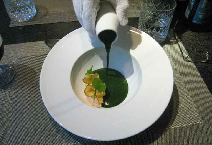 A gloved-hand pours the Nettle soup with Karelian trout sorbet and willow-tea