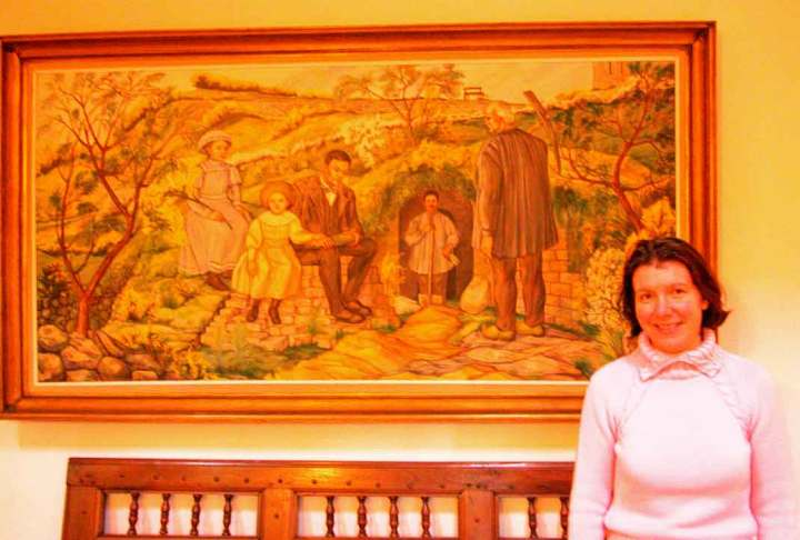 The maîtresse of 'An Ti Gwenn' standing in front of an image of her archaeologist grandfather at work.