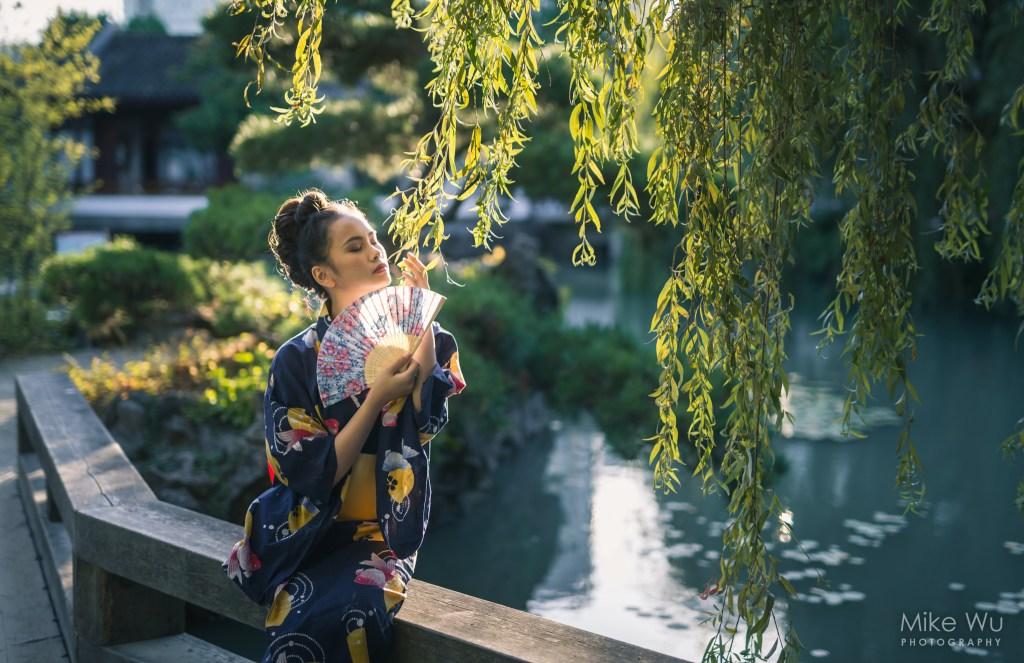 vancouver portrait photographer mike wu asian japanese garden female traditional fan willow tree lake koi bridge published backlit beauty serene peaceful