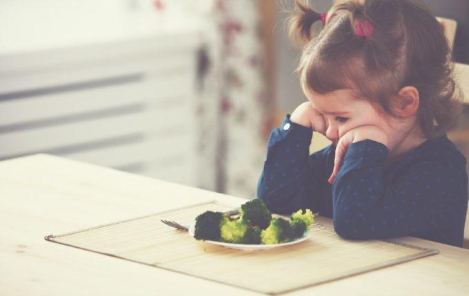 Kind schmollt vor Teller mit Brokkoli