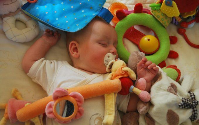 Baby schläft mit Schnuller im Mund umgeben von Spielzeug