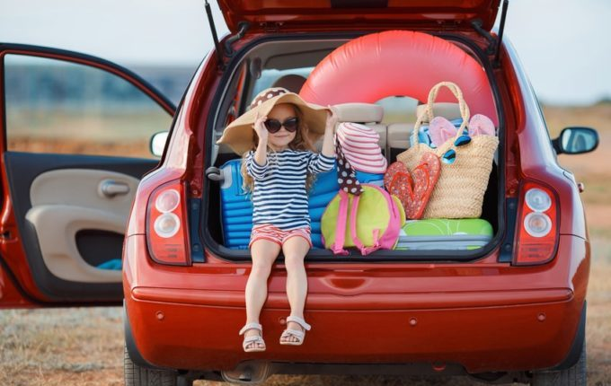 6 Tipps, um eine lange Autofahrt mit Kleinkind zu überstehen - Kind mit Gepäck im Koferraum