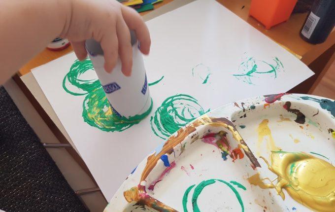 Kind tunkt Klopapierrolle in Farbe und macht Muster auf Papier