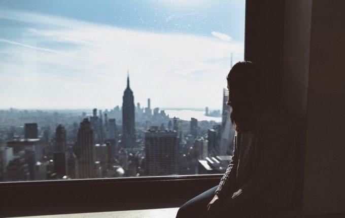 Frau sitzt traurig am Fenster
