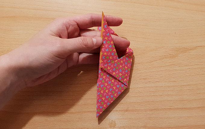 Finger nehmen Flügel vom Origamipapier in die Hand