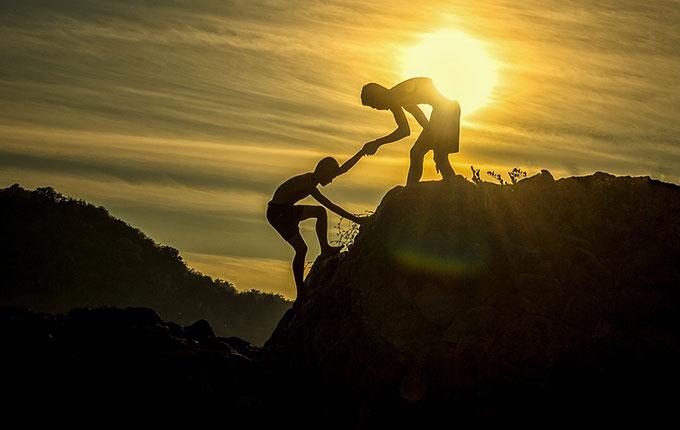 Mann hilft anderem Mann den Berg hoch