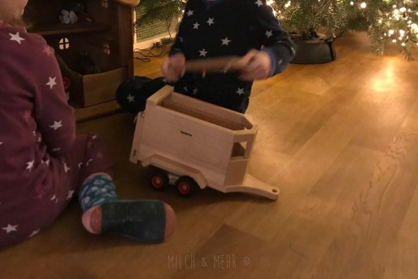 Spielen mit Fagus Anhaenger und Holzbauernhof unter Weihnachtsbaum