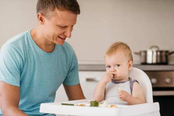 pai observando o bebê comer sozinho